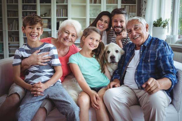 Ritratto della famiglia felice che si siede sul sofà in salone