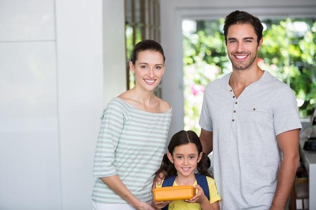 Ritratto della famiglia sorridente con la scatola di pranzo della tenuta della figlia