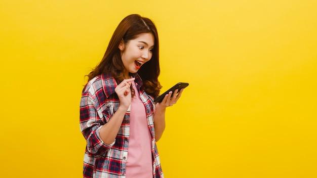 Ritratto della femmina asiatica sorpresa che per mezzo del telefono cellulare con l'espressione positiva, vestita in abbigliamento casual ed esaminando macchina fotografica sopra la parete gialla. la donna felice adorabile felice si rallegra del successo.