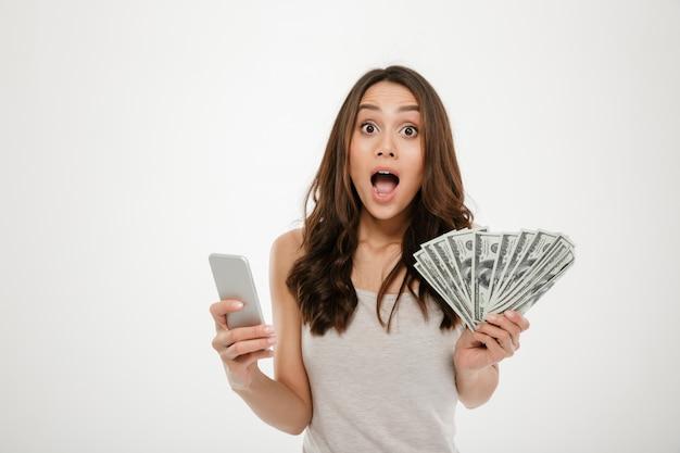 Ritratto della femmina attraente 30s del brunette che vince i lotti della valuta del dollaro dei soldi per mezzo del suo smartphone, essendo sopra bianco allegro