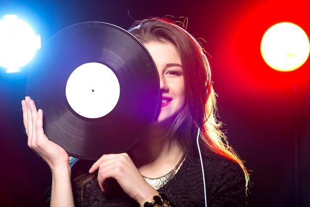 Ritratto della femmina dj con disco in vinile.