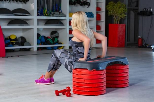 Ritratto della femmina sportiva che fa esercizio fisico in palestra