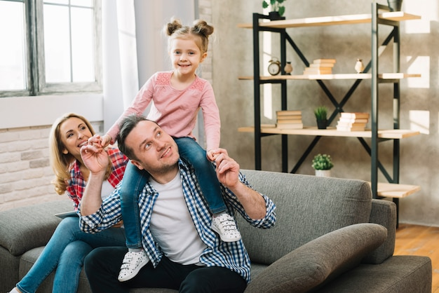 Ritratto della figlia felice che si siede sulla spalla di suo padre con sua madre