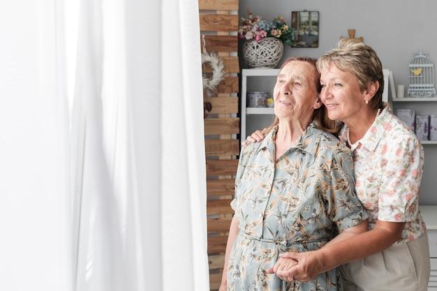 Ritratto della figlia matura con sua madre senior a casa