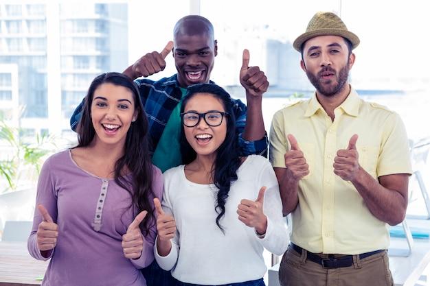 Ritratto della gente di affari creativa con i pollici su in ufficio