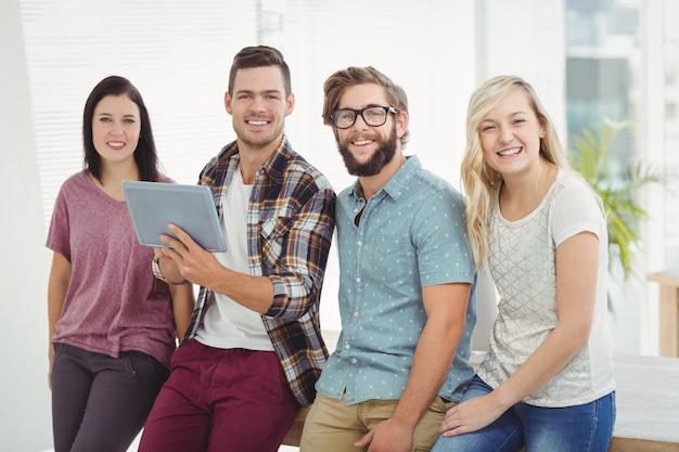 Ritratto della gente di affari sorridente che tiene compressa digitale