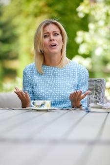 Ritratto della giovane donna arrabbiata che risolve i problemi di business che si siedono nella caffetteria moderna. giovane donna graziosa che gode del tempo libero nell'interno del caffè