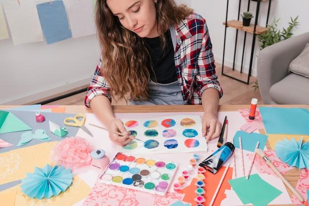 Ritratto della giovane donna che dipinge cerchio astratto su libro bianco