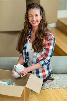 Ritratto della giovane donna che disimballa i contenitori di cartone in nuova casa