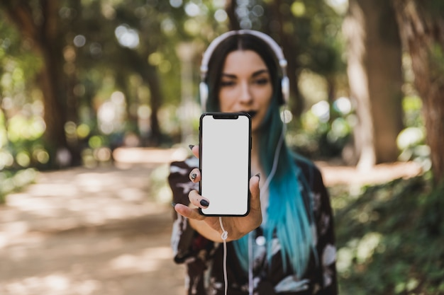 Ritratto della giovane donna che mostra lo smart phone bianco in bianco