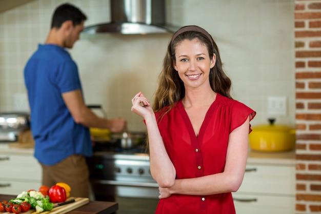 Ritratto della giovane donna che sorride nella cucina mentre uomo che cucina sulla stufa