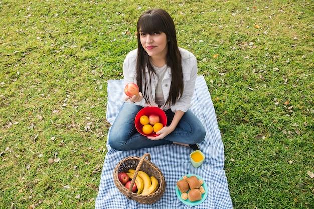Ritratto della giovane donna che tiene frutta fresca nel parco