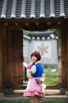 Ritratto della giovane donna del costume di hanbok che guarda e che sorride nel parco coreano