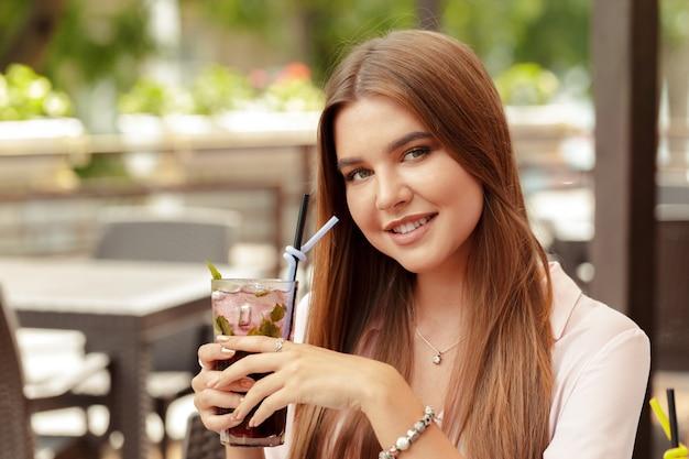 Ritratto della giovane donna deliziosa che tiene vetro di cocktail rinfrescante freddo