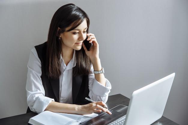 Ritratto della giovane donna esecutiva che si siede allo scrittorio e che lavora al computer portatile mentre facendo chiamata