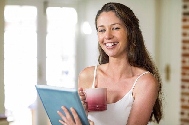 Ritratto della giovane donna felice che tiene tazza di tè e che utilizza compressa digitale nella cucina