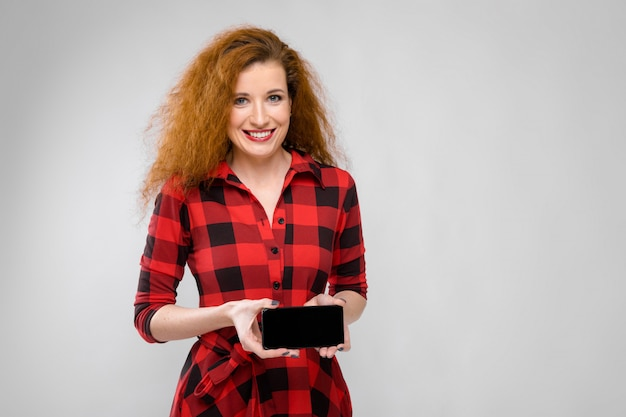 Ritratto della giovane donna felice della bella testarossa in vestito a quadretti che sorride mostrando telefono cellulare