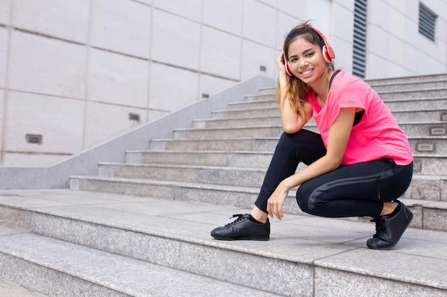 Ritratto della giovane donna sorridente che hunkering in cuffie all'aperto