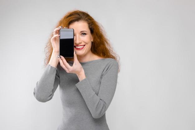 Ritratto della giovane donna sorridente felice della bella testarossa in vestiti grigi che mostrano telefono cellulare