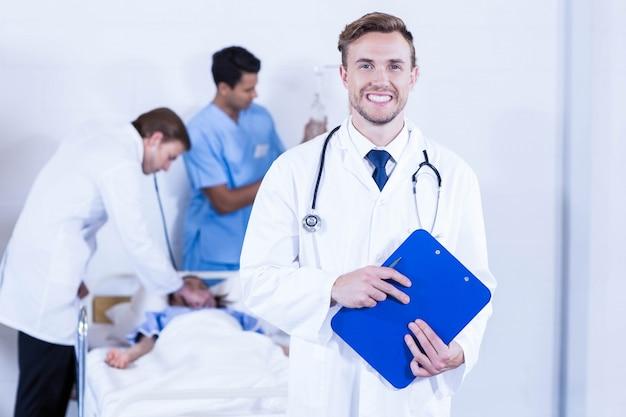 Ritratto della lavagna per appunti della tenuta di medico e di altro medico che esaminano un paziente dietro in ospedale