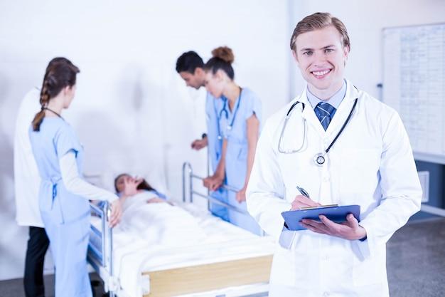 Ritratto della lavagna per appunti della tenuta di medico e di altro medico che esaminano un paziente dietro
