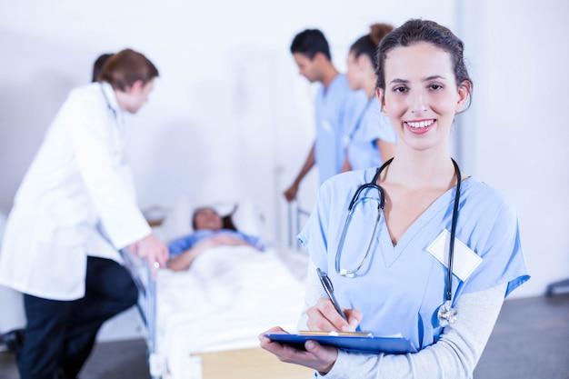 Ritratto della lavagna per appunti femminile della tenuta di medico e di altro medico che esaminano un paziente dietro