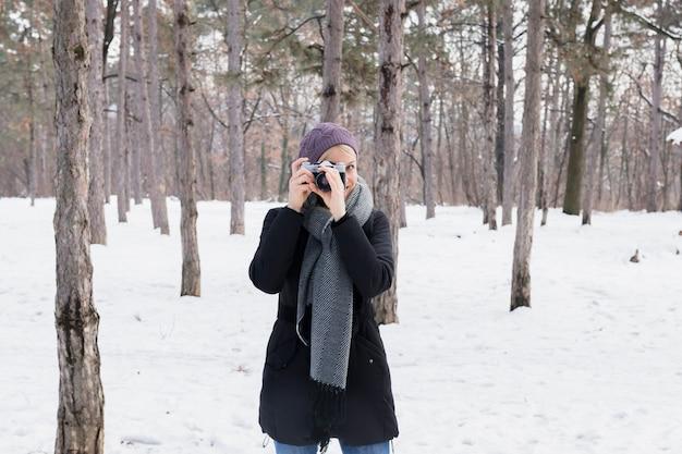 Ritratto della macchina fotografica della tenuta della giovane donna nel paesaggio nevoso