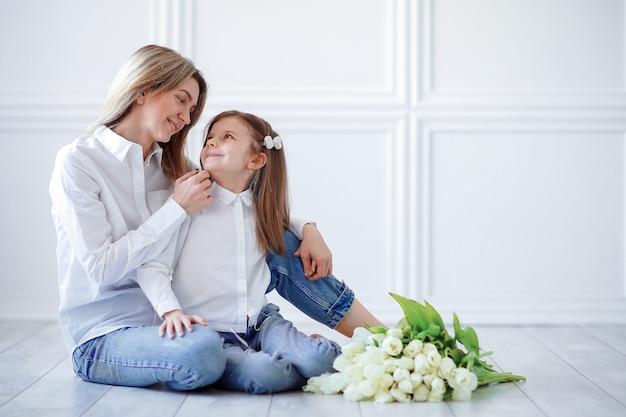 Ritratto della madre amorosa della bambina che la tiene e tulipani