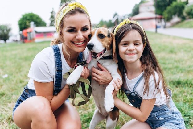 Ritratto della madre e della figlia che abbracciano cane all'aperto.