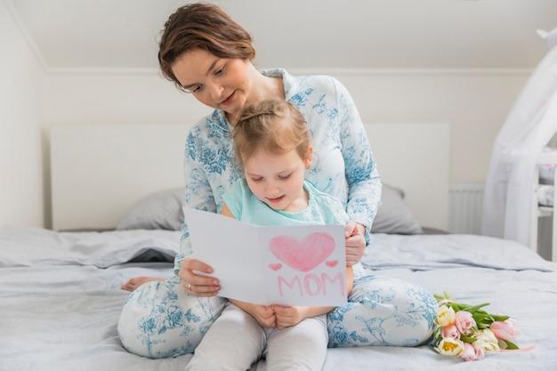 Ritratto della madre e della figlia che leggono cartolina d'auguri sul letto a casa