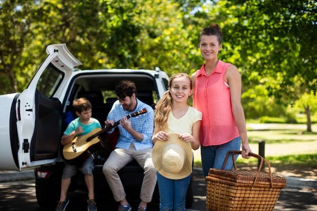 Ritratto della madre e della figlia che stanno con il canestro di picnic mentre padre e figlio che giocano chitarra in b