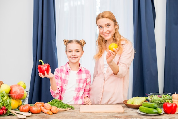 Ritratto della madre e della figlia che tengono limone giallo e peperone rosso a disposizione che esaminano macchina fotografica