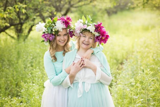 Ritratto della madre e della figlia sorridenti che posano e che abbracciano in corone dei fiori all'aperto sulla a degli alberi.