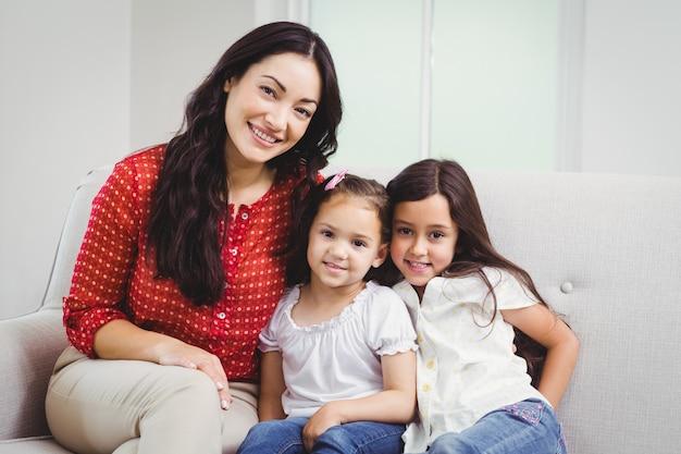 Ritratto della madre e delle figlie sorridenti a casa