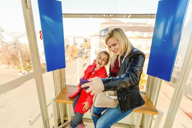 Ritratto della madre felice e del bambino che parlano in grande ruota panoramica.