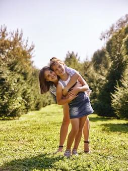 Ritratto della madre felice e della neonata che abbracciano nel parco