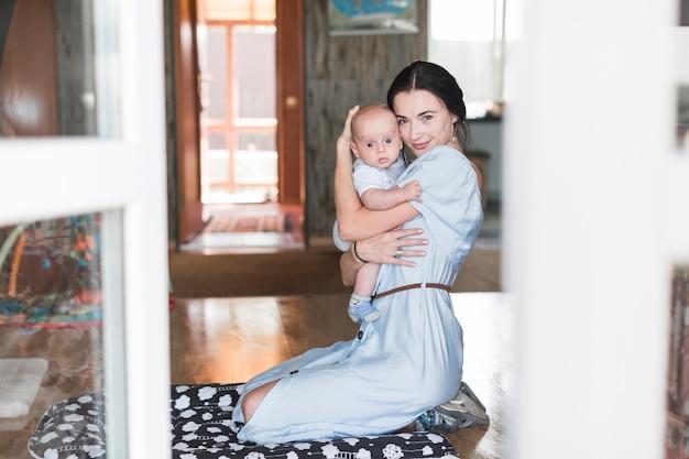 Ritratto della madre sorridente che abbraccia il suo bambino a casa