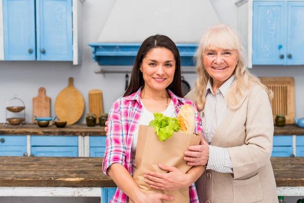 Ritratto della madre sorridente che sta con la sua borsa di drogheria della tenuta della figlia