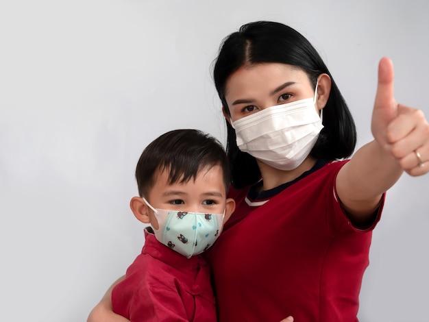 Ritratto della mamma e del figlio asiatici della famiglia che mostrano pollice su e indossano la maschera