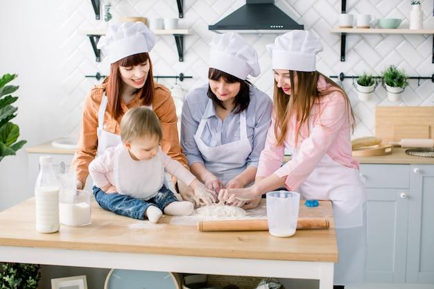 Ritratto della nonna con le sue figlie e la nipote che fanno insieme cena in cucina. concetto di festa della mamma.