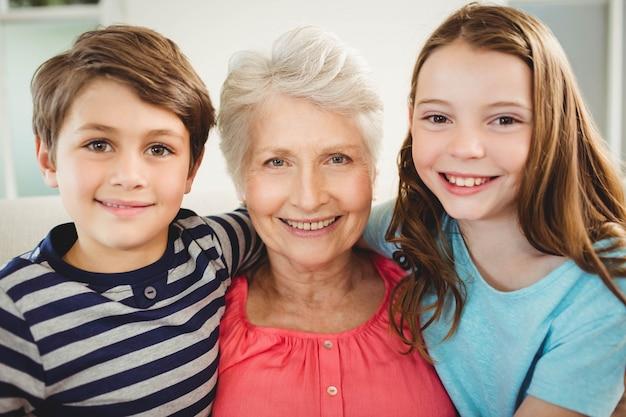 Ritratto della nonna e dei nipoti che si siedono insieme sul sofà in salone
