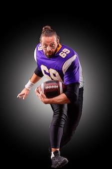 Ritratto della palla di lancio del giocatore di football americano sopra la parete nera
