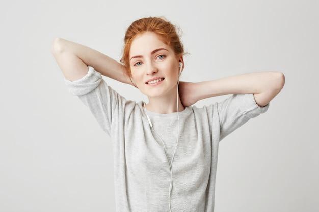 Ritratto della ragazza abbastanza sexy che ascolta la musica nel sorridere delle cuffie. mani dietro la testa.