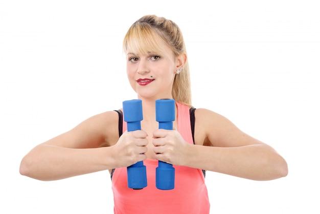 Ritratto della ragazza abbastanza sportiva che tiene peso