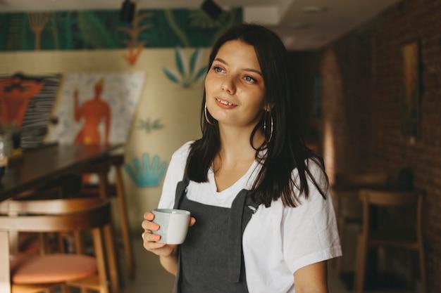 Ritratto della ragazza affascinante sorridente del brunette con le parentesi graffe sui denti in abbigliamento casual con la tazza di caffè in caffè