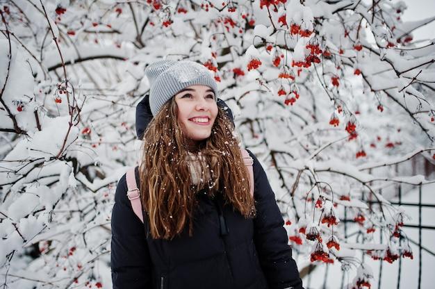 Ritratto della ragazza al giorno nevoso di inverno vicino agli alberi innevati.