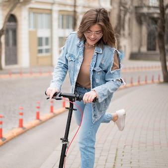 Ritratto della ragazza alla moda che guida motorino elettrico