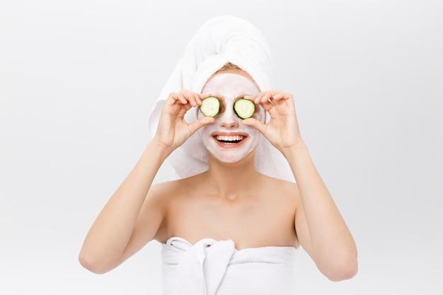 Ritratto della ragazza allegra che copre un occhio da una fetta di un cetriolo, isolato su bianco.