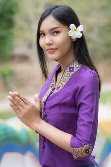 Ritratto della ragazza asiatica in preghiera tradizionale del laos del vestito.