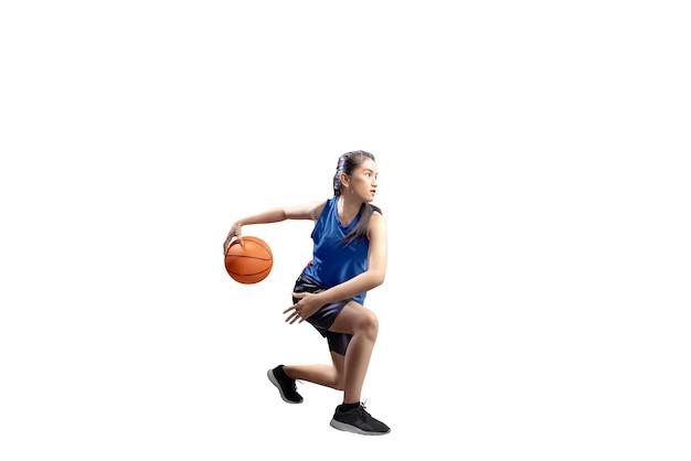 Ritratto della ragazza asiatica in uniforme sportiva blu sui movimenti del perno di pallacanestro